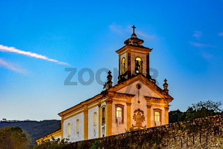 Old and historic 18th century church with its facade illuminated at dusk