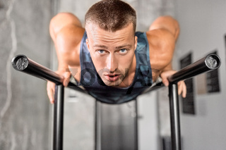 man doing push-ups on parallel bars in gym