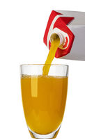 Pouring orange juice from bottle into glass