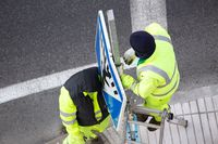 Workers changing a damaged road sign on street sidewalk