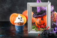 Pumpkin in witch's hat and Halloween ghost cupcakes.