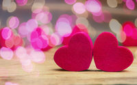 Small wooden hearts with pink bokeh effects