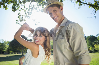 Cute couple dancing in the park smiling at camera