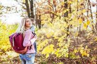 Happy travelers go to the autumn forest holding hands to meet new adventures. Focus on the charming blonde in the foreground who turned around looking at the camera. Togetherness with nature concept