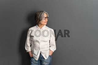 Beautiful mature lady in glasses stands hands in pockets looking at side. Elegant Gray-haired woman in whiite shirt on gray background. Copy space for text at right side