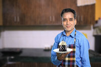 Indian Male Chef with a Sweet Cake with Kitchen Interiors