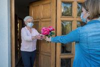 Seniorin mit Mundschutz bekommt Blumenstrauß von Nachbarin an der Haustür