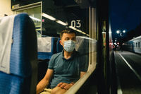 Tired and sad male passenger sits in face shield and looks through the window. View through the window. Topic passenger public transport during coronavirus pandemic. New rules of life covid 19