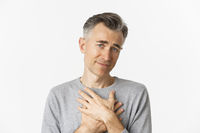 Close-up of thankful middle-aged man, holding hands on heart and feeling touched, appreciate kind gesture, standing over white background