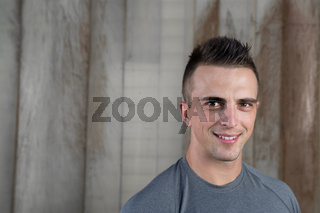 Portrait of strong and sporty young man after fitness exercise on rustic background