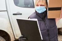 Lieferdienst Paketbotin mit Mundschutz überprüft Liste