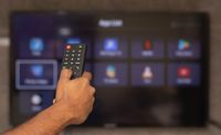 Maski, India 18,January 2020 - Hands holding remote control with different online subscription apps on TV screen in out of focus