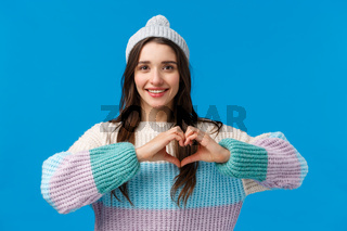 Valentines day, relationship and emotions concept. Lovely, pretty brunette girl in winter hat, sweater, showing heart sign and smiling, looking camera happy, show love and affection, blue background