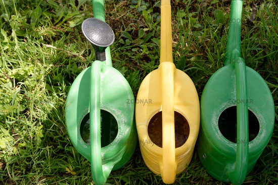 Row of three colorful watering cans in a garden