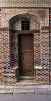 Grunge wooden decorated arched gate with inner small door on wall with black and red bricks