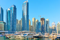Yachts and boats neat towers of Dubai Marina