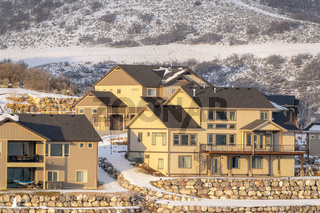 Lovely homes on hilly neighborhood terrain amid natural snowy scenery in winter