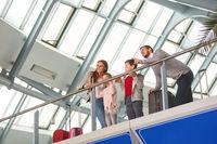 Familie mit Kindern im Flughafen unterwegs