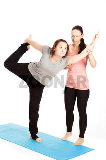 Yoga teacher provides assistance in training, Shiva natarajasana