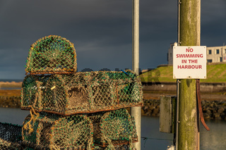 Sign: No swimming in the harbour - and some fish traps