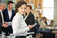 Frau im Büro tippt auf Smartphone