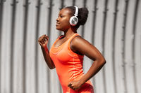 happy african american woman running outdoors