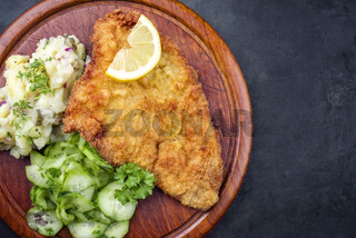 Traditional deep-fried schnitzel with potato and cucumber salad offered as top view on a rustic wooden board with copy space right