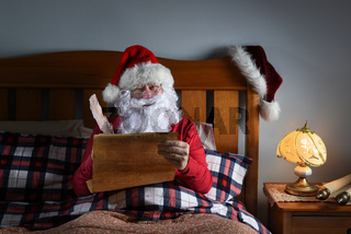Santa Claus sitting up in his bed working on his naughty and nice list.