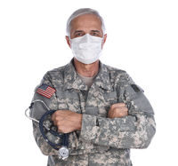 Military Health Care Concept. Military doctor with his arms folded wearing camoflague fatigues, surgical mask holding a stethoscope.