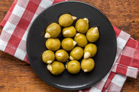 Pitted green olives stuffed with almonds on plate.