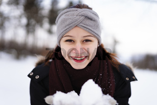Laughing girl in winter clothes with snow