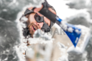Man clear snow from car with cleaning tool