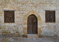 Old weathered arched wooden door and two closed rusted wrought iron windows on bricks stone wall