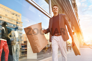 Serious stylish young man walking in urban street and enjoying Black Friday shopping in trendy stores in city