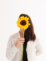 Caucasian woman covering her face with sunflower on white background
