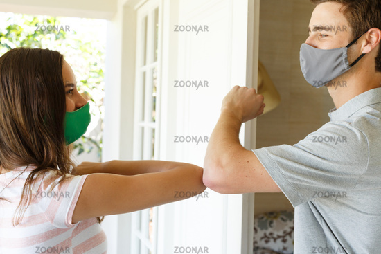 Caucasian couple wearing face masks greeting by elbow bumping