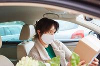 Frau in Auto mit Mundschutz prüft Paket nach Abholung