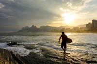 Surfer on Ipanema beach at sunset