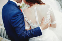 Groom hugs bride back in white dress. Blurred background