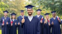 happy male graduate student showing thumbs up