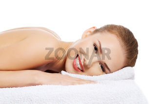Beautiful caucasian naked woman lying on a massage table and relaxing.