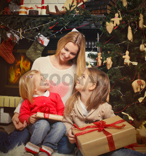 Young mother and her two little daughters with Christmas gifts by a Christmas tree in cozy living room in winter