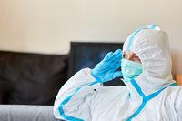 Pflegepersonal in Klinik Pausenraum in Schutzkleidung ist nachdenklich