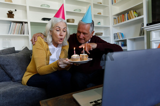 Senior caucasian couple celebrating birthday while having a video chat on laptop at home