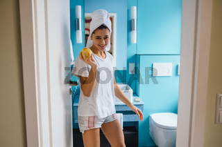 Young caucasian woman in bathroom, hold apple.