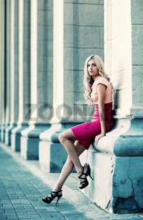 woman is leaning on a column