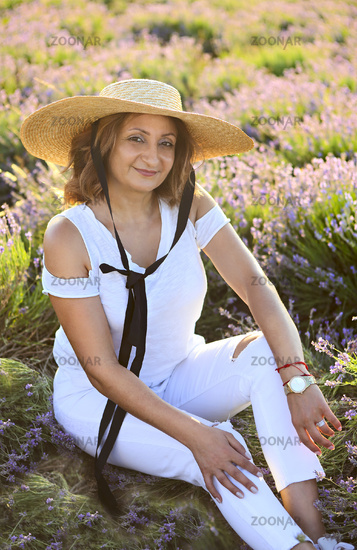 Happy middle age blond woman in white posing on lavender field