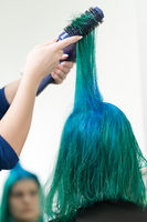 Hairdresser combs and dries hair of emerald color with hairdryer after dyeing hair roots in color of lapis lazuli