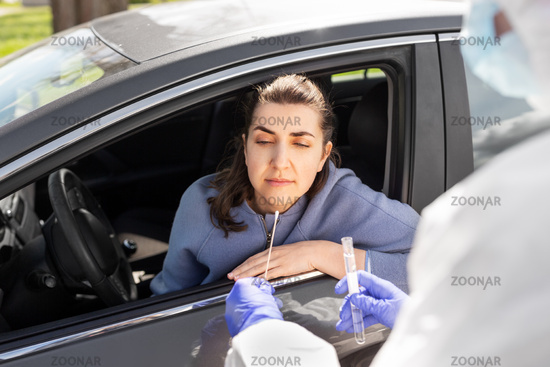 healthcare worker making coronavirus test at car