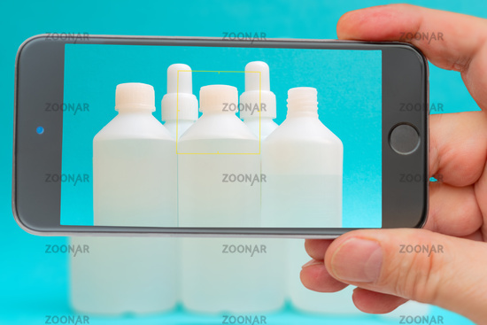 Antiseptic vials on smartphone screen. Disinfectant liquid in a white bottle. Therapeutic drug. Disinfection against coronavirus.